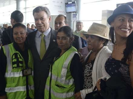President Santos in Bogotá's El Dorado International Airport, flanked by 2 airport employees. Photo credit: Efraín Herrera
